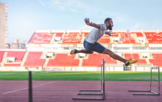 man jumping over hurdles as metaphor for overcoming digital transformation challenges