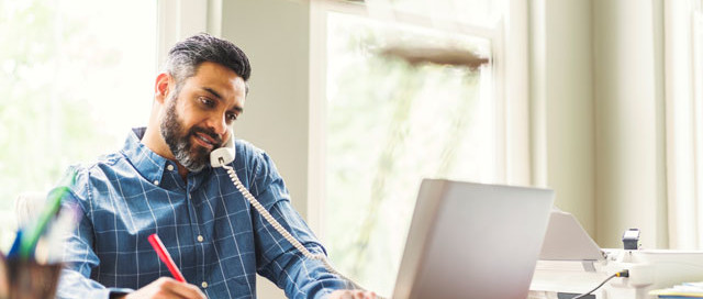 Man working remotely with DaaS, and talking on telephone with his laptop open